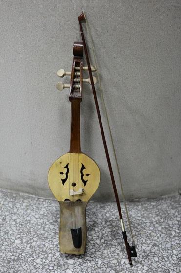 呈长方形,用整块木头雕凿而成,木盆状音室,类似汉民族的古琴和古筝式
